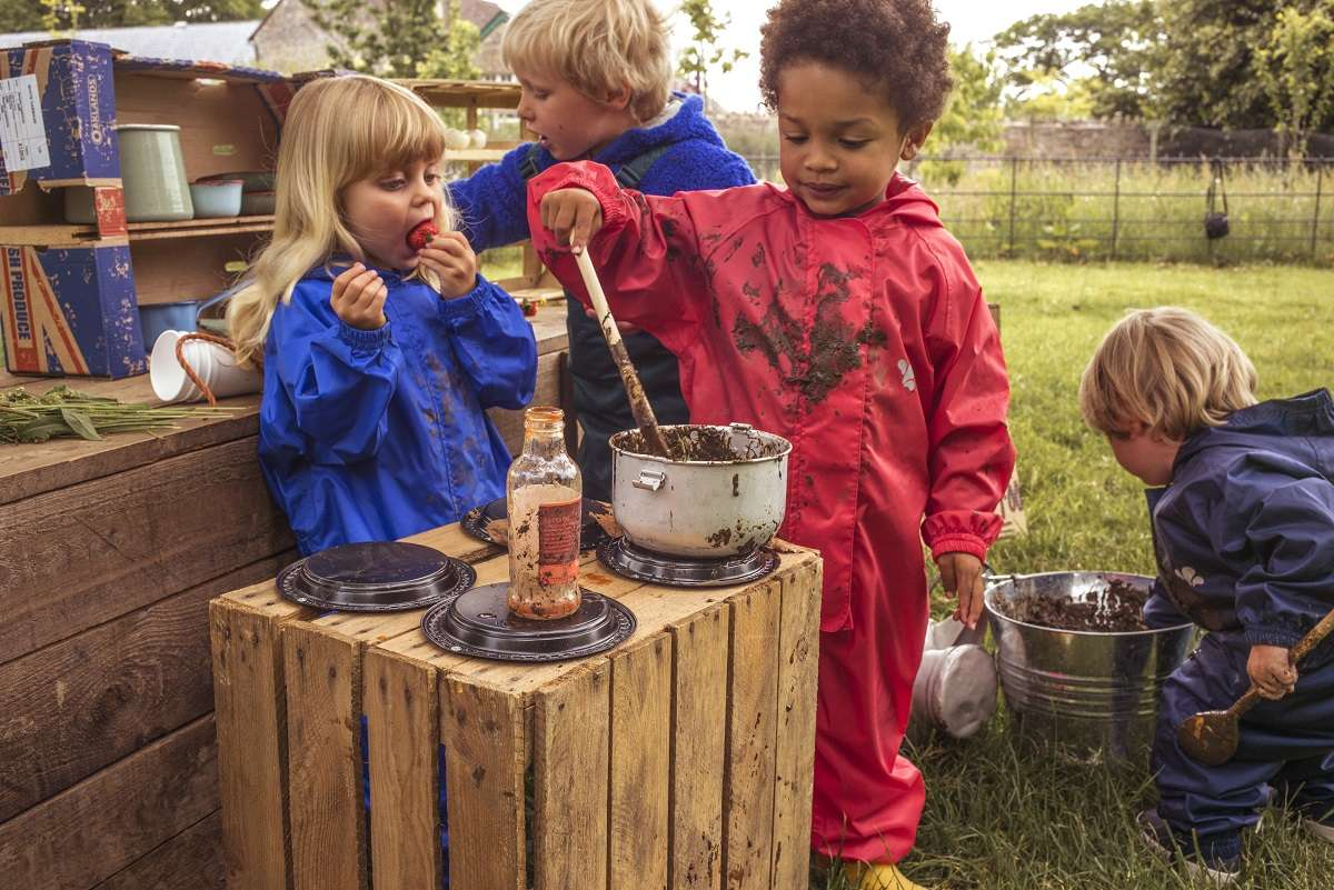 children playing with a mud kitchen