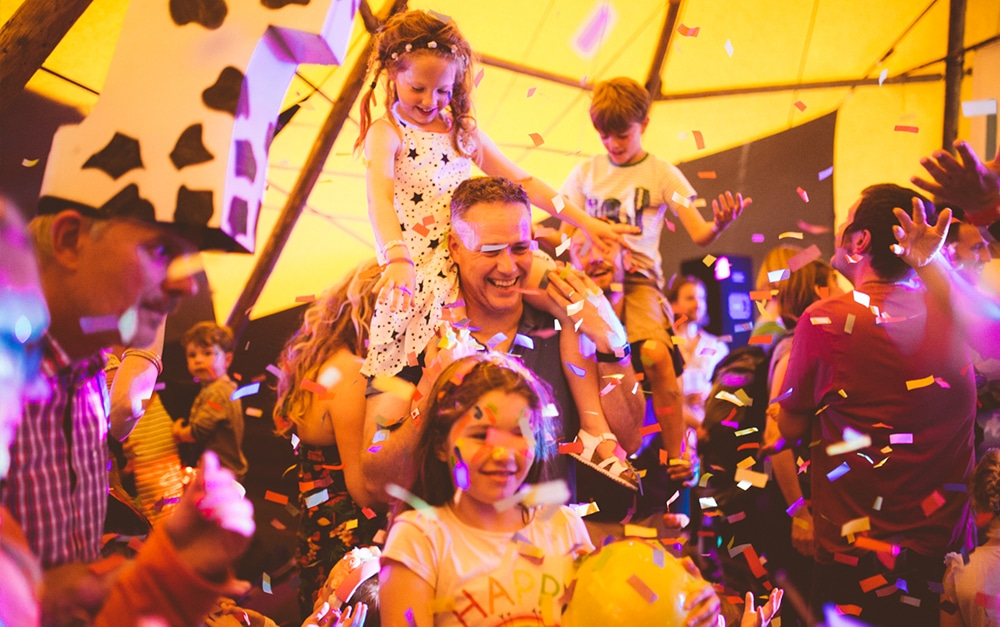 family dancing in a festival tent with confettis
