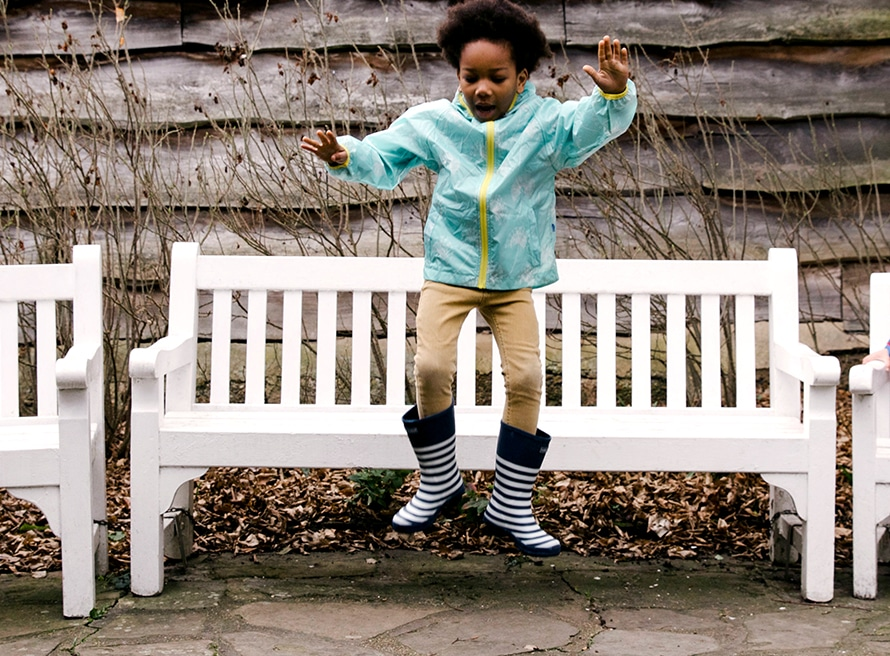 little boy jumping from bench wearing Muddy Puddles waterproof jacket