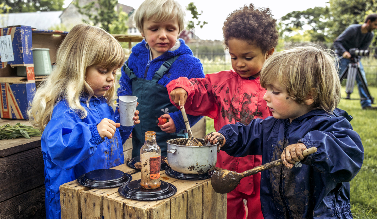 Nursery school children Outdoor Learning with a mud kitchen