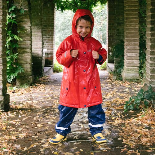 boy in the rain with protective waterproof jacket
