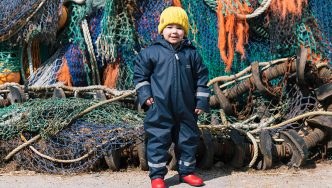 toddler wearing muddy puddles puddleflex suit
