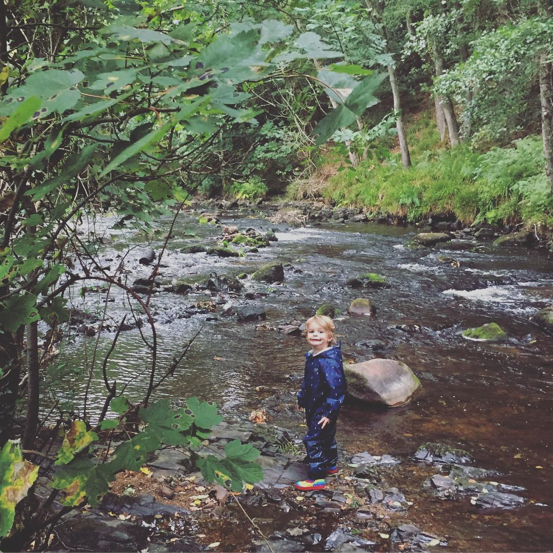 boy by a stream wearing Muddy Puddles scampsuit