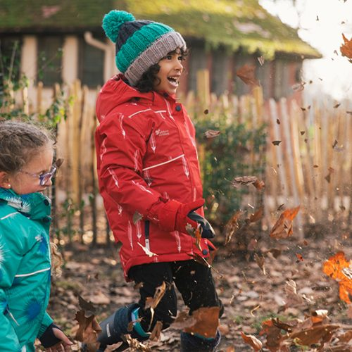 Children playing in autumn leaves wearing MP blizzard Jacket