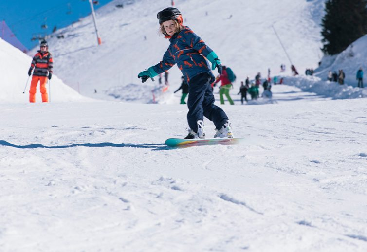 boy snowboarding wearing Muddy Puddles blizzard jacket and salopette