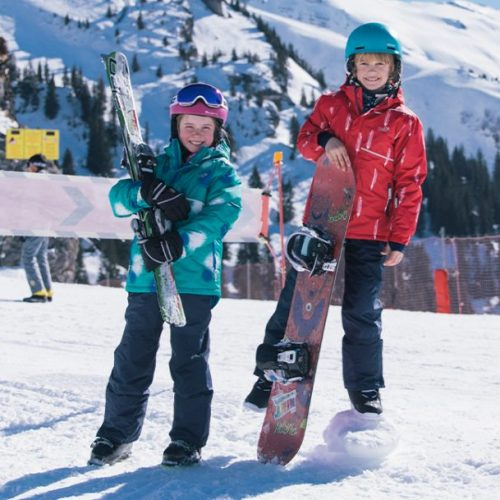 children on ski slope wearing blizzard jackets and salopette