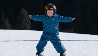 little boy skiing wearing muddypuddles scampsuit