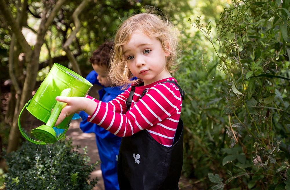 little girl with green watering can