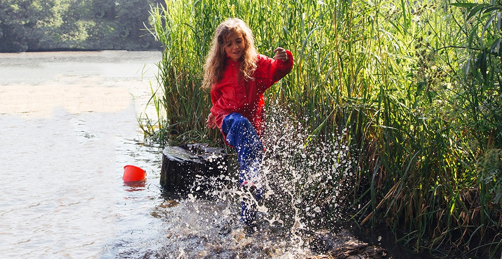 girl splashing water in a pond in waterproof clothes