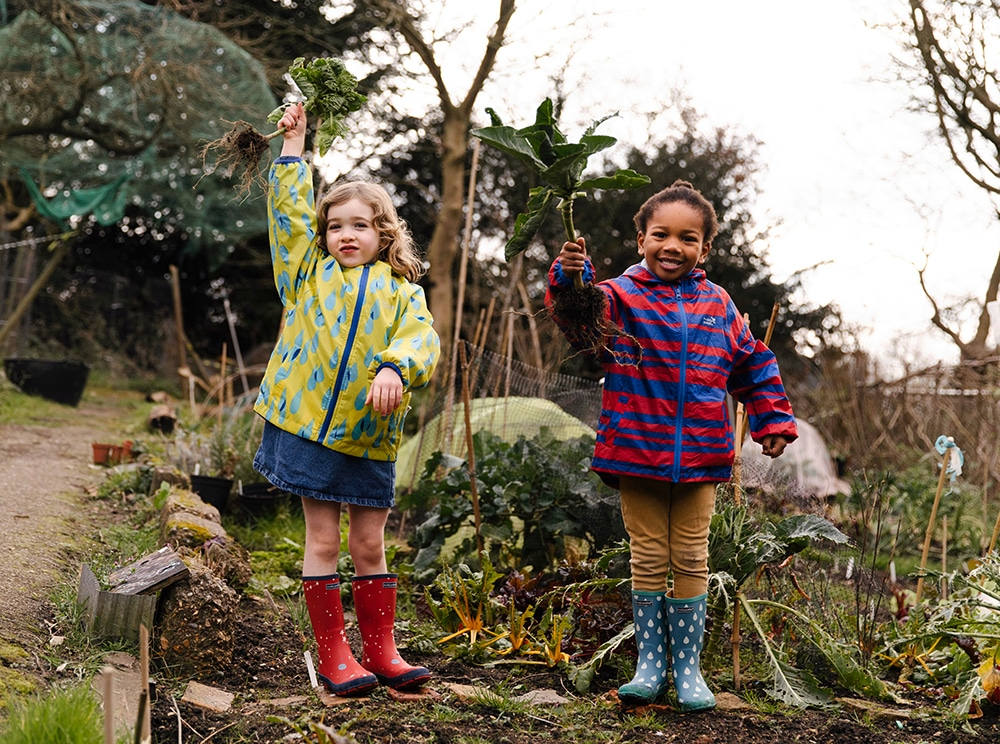 children in garden holding vegetables