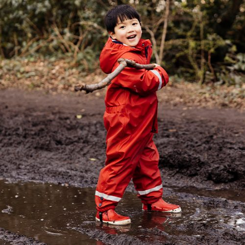 boy playing in the mud with a stick