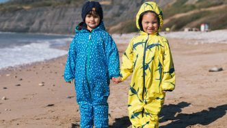 children on the beach wearing protective waterproof recycled suits