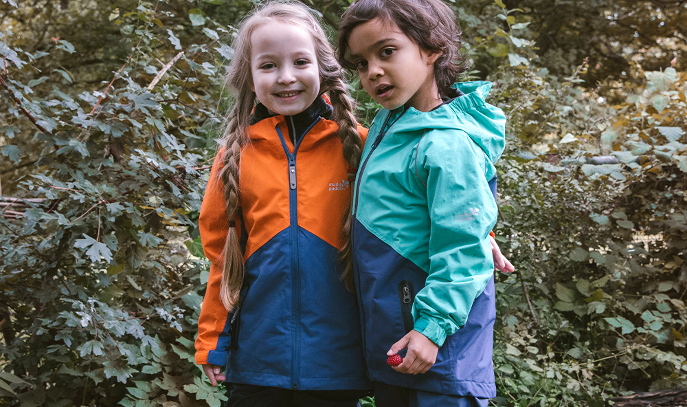 girl and boy in a garden wearing hardshell jacket